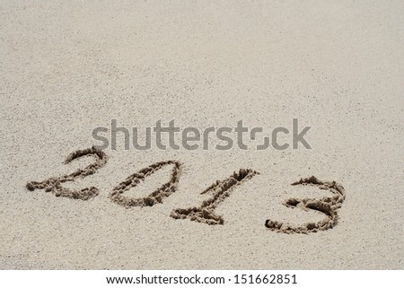 Concept or conceptual hand made or handwritten 2013 year text in sand on a beach in an exotic island as metaphor to tropical,summer,sea,ocean,calendar,travel,holiday,sunny,tourism,resort,time or relax - stock photo