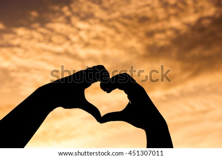 Concept or conceptual heart shape or symbol made of human or woman and man hand silhouette over a sky at sunset background for love, valentine, romantic, couple, wedding, romance, summer or sunrise - stock photo