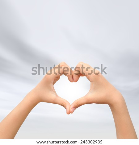 Concept or conceptual human male man and woman hands in love, Valentines shape or symbol heart over blue sky background, metaphor to romance, romantic, wedding, honeymoon, holiday, vacation or couple - stock photo