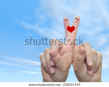 Concept or conceptual human or female hands with two fingers painted with a red heart and smile faces over cloud blue sky background for valentine, romantic, love, couple, young, family or wedding - stock photo