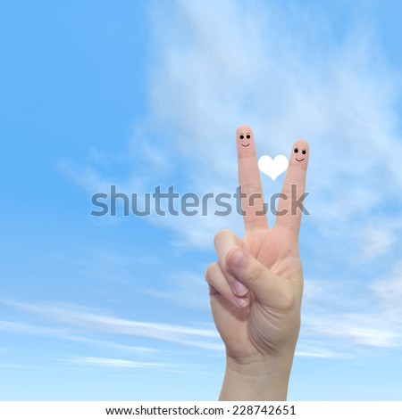 Concept or conceptual human or female hands with two fingers painted with a white heart and smiley faces over cloud blue sky background for valentine, romantic, love, couple, young, family or wedding - stock photo