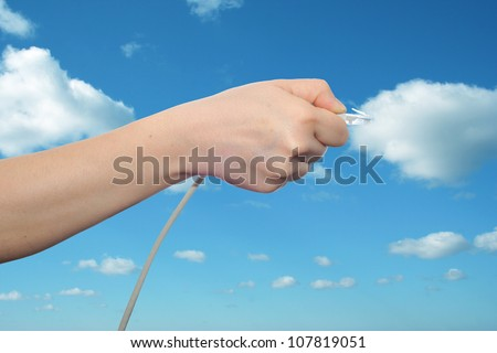 Concept or conceptual human or man hand holding a internet data cable in clouds over the blue sky, as a metaphor for plug, connection, technology, share, network, mobility, connectivity or communication - stock photo
