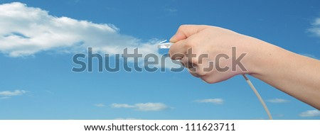 Concept or conceptual human or man hand holding a internet data cable in clouds over the blue sky, as a metaphor for plug,connection,technology,share,network,mobility,connectivity or communication - stock photo