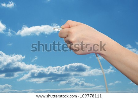 Concept or conceptual human or man hand holding internet data cable in clouds over the blue sky, as a metaphor for plug, connection, technology, share, network, mobility, connectivity or communication - stock photo