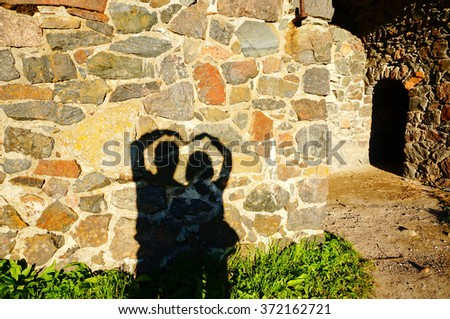 Concept or conceptual Valentine human man and woman hands silhouette as heart or love symbol on stone wall - stock photo