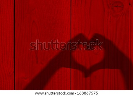 Concept or conceptual Valentine human man and woman hands silhouette as heart or love symbol on old red wood background,metaphor to romantic,romance,relationship,young,couple,emotions,wedding or lover - stock photo