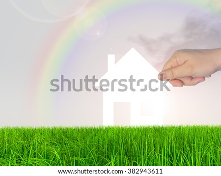 Concept or conceptual white paper house held in hand by a man in a green summer grass over a rainbow sky background with clouds for construction, eco, ecology, loan, mortgage, property or home