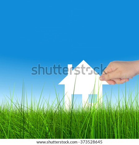 Concept or conceptual white paper house held in hand by a man in a green summer grass over a blue sky background with clouds a symbol for construction, eco, ecology, loan, mortgage, property or home - stock photo