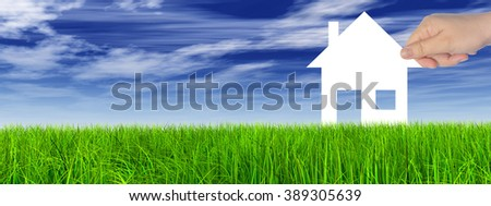 Concept or conceptual white paper house held in hand by a man in a green summer grass over a blue sky background with clouds, a symbol for construction, eco, ecology, loan, mortgage, property or home - stock photo