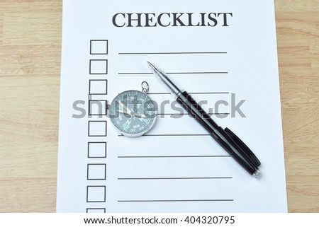 Concept : pen on paper with checklist word on wood background - stock photo