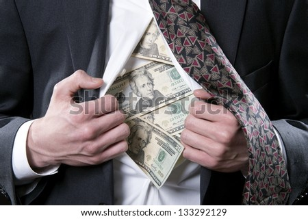Concept photo for hidden money showing a businessman pulling back his shirt and tie exposing twenty dollar bills - stock photo