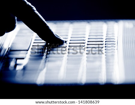 Concept photo in high contrast black and white of hacker's single finger on keyboard - stock photo