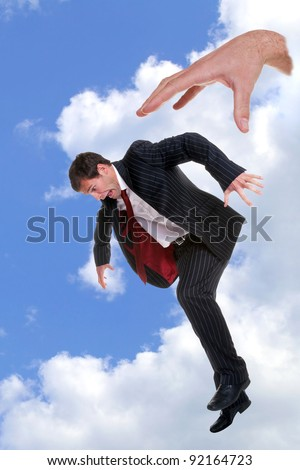 Concept photo of a businessman being dropped out of the sky by the hand of God, could be used to portray themes such as fear, fright, nightmare, refusal, dismissal, rejection, failure or disapproval. - stock photo