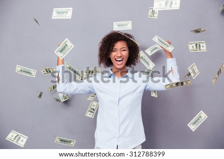 Concept photo of a cheerful afro american woman standing under rain with money on gray background - stock photo