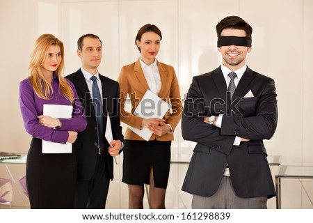 concept photo of a young businessman having eyes covered, with his partners in the background, smiling