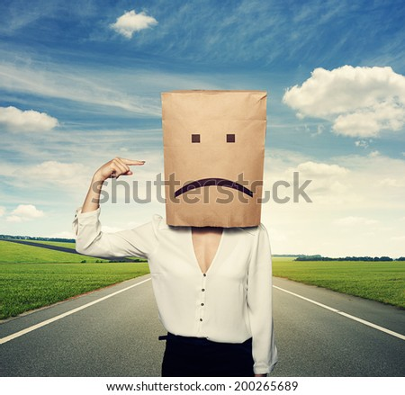 concept photo of bad mood. woman with paper bag on the head - stock photo