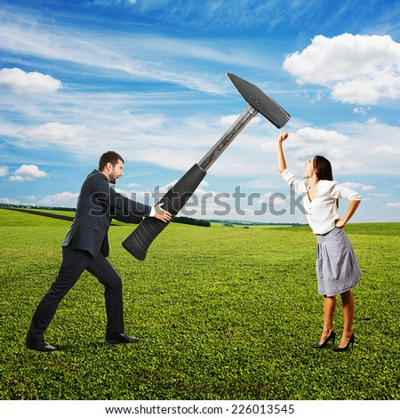 concept photo of conflict between man and woman. angry screaming man holding big hammer and hitting, woman showing fist and shouting. photo at outdoor