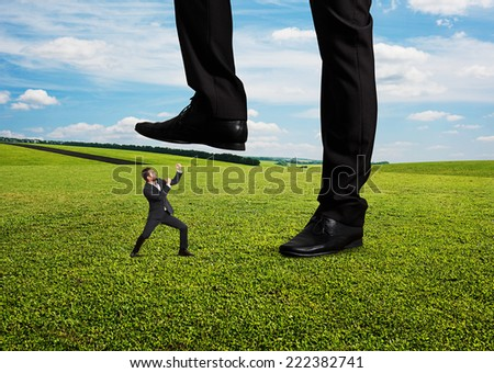 concept photo of conflict between subordinate and boss. angry young businessman showing fist and looking up at his boss. photo at outdoor - stock photo