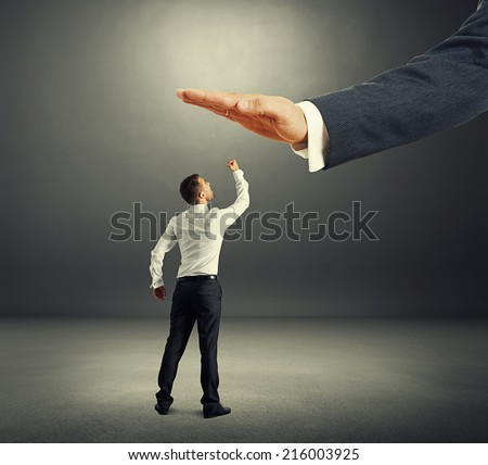 concept photo of conflict between subordinate and boss. dissatisfied businessman looking up at big palm of his boss and showing in the dark room - stock photo