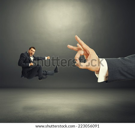 concept photo of conflict between subordinate and boss. emotional young businessman kicking and screaming, big hand flicking. photo in the dark room - stock photo