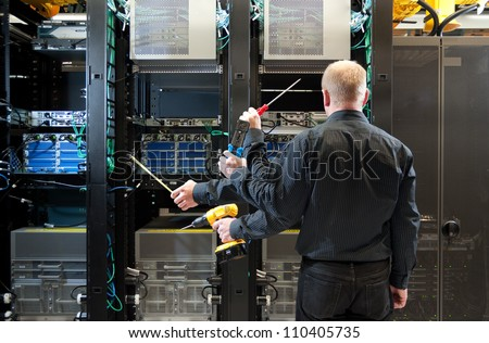 Concept photo of Network administrator installing equipment. Multiple tools shown with multiple hand positions. - stock photo