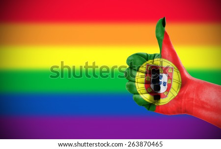 Concept photo - Positive attitude of Portugal for LGBT community. Hand against rainbow flag. Focus set on hand. - stock photo