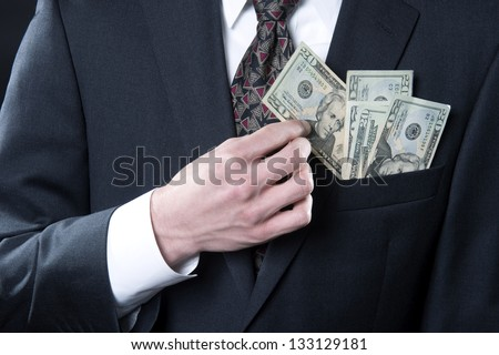 Concept photo showing businessman with money in pocket pulling out twenty dollar bill - stock photo