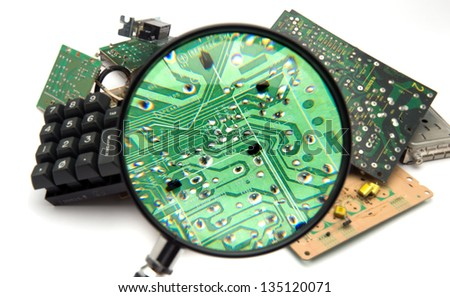 Concept photo showing digital computer parts discarded in garbage pile examined with magnifying glass - stock photo