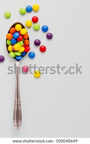 Concept photograph of a spoon full of colored chocolate buttons representing unhealthy diet. - stock photo
