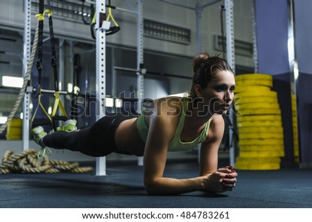 Concept: power, strength, healthy lifestyle, sport. Powerful attractive muscular woman CrossFit trainer stand in plank during workout at the gym