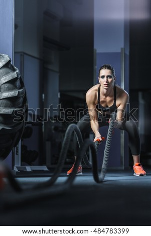 Concept: power, strength, healthy lifestyle, sport. Powerful attractive muscular woman CrossFit trainer do battle workout with ropes at the gym