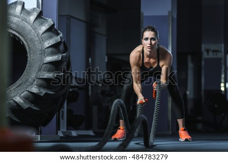 Concept: power, strength, healthy lifestyle, sport. Powerful attractive muscular woman trainer do battle workout with ropes at the gym