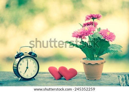 Concept red heart with bouquet of flower and alarm clock on table in garden with bokeh green leaf background. Retro filter.Valentines Day background. - stock photo