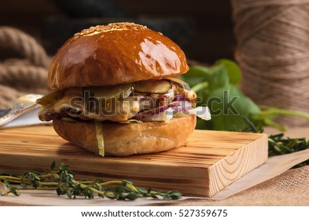 Concept: restaurant menus, healthy eating, homemade, gourmands, gluttony. Trendy glossy burger with chicken with ingredients on messy vintage wooden background.