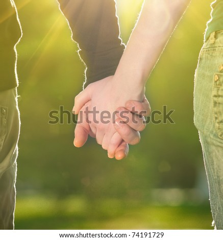 Concept shoot of friendship and love of man and woman: two hands over sun ray and nature - stock photo