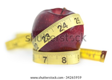 "Concept shot for healthy eating to achieve slimming and the perfect waist size Very shallow focus on 24"". Isolated on white with slight shadows around measuring tape left behind intentionally."
