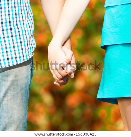 Concept shot of friendship and love of man and woman: two hands over fall autumn nature park - stock photo