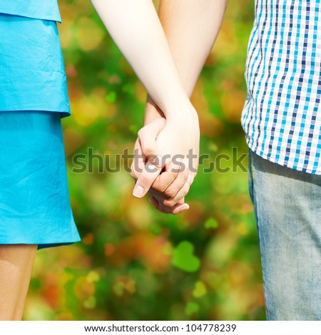 Concept shot of friendship and love of man and woman: two hands over green nature park - stock photo