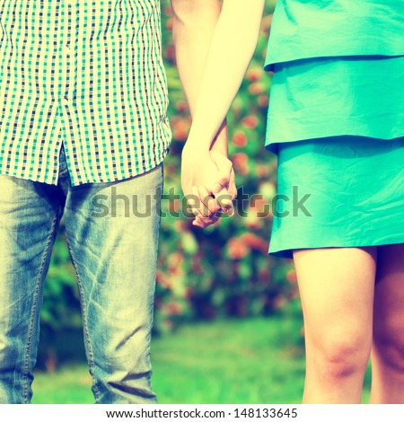 Concept shot of friendship and love of man and woman: two hands over green nature park. Grunge retro style. - stock photo