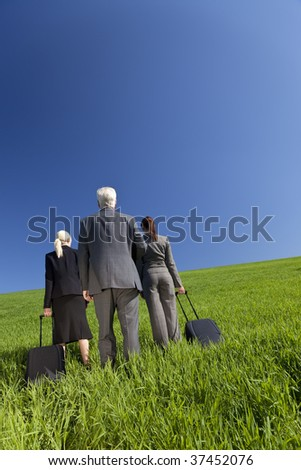 Concept shot showing three business executives, one male and two female, walking through a green field towards the horizon. Environmental, business and travel concepts, shot on location. - stock photo