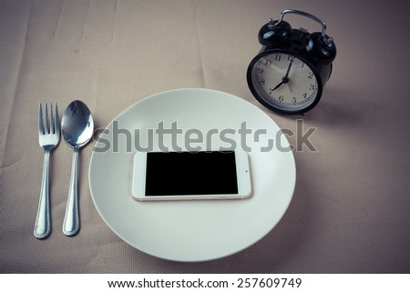 Concept smartphone put in empty dish on table with alarm clock.