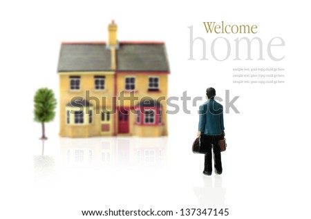 Concept stock photograph depicting coming home. Man carrying cases approaching property against a white background. Copy space. - stock photo