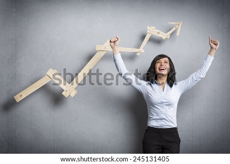 Concept: Success in business or career. Enthusiastic businesswoman with raised arms cheering in front of positive business graph, isolated on grey background. - stock photo