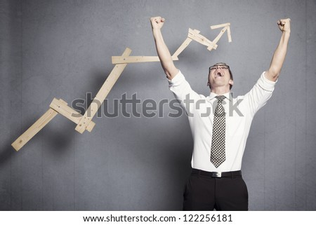 Concept: Success in business. Overjoyed talented businessman with raised arms cheering in front of positive business graph, isolated on grey background. - stock photo