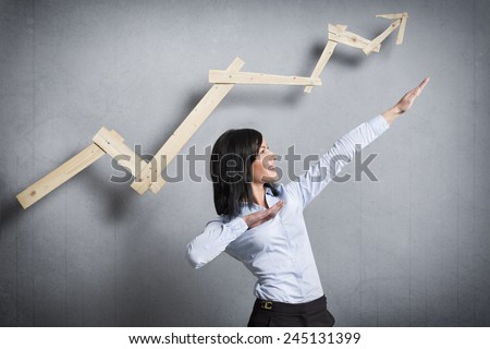 Concept: Successful business trend. Happy talented businesswoman pointing arm upwards in front of ascending business graph, isolated on grey background. - stock photo