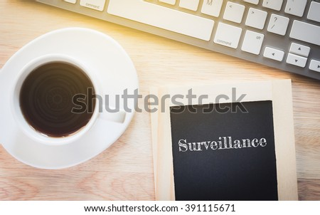 Concept Surveillance message on wood boards. A keyboard and a glass coffee table.Vintage tone. - stock photo