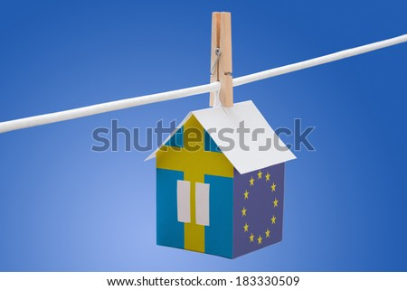 concept - sweden, swedish and EU flag painted on a paper house hanging on a rope - stock photo