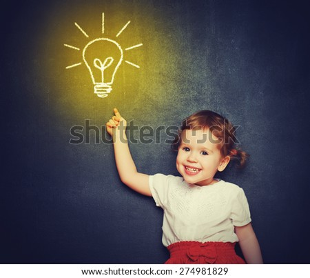 concept, the idea of a happy little girl with a bulb at the blackboard - stock photo