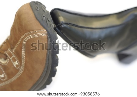 Concept to illustrate a union/partnership using a male boot with a female shoe. Very short depth of field. - stock photo
