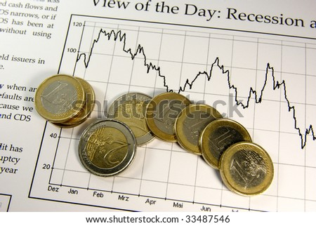 Concept towards economic recession. Euro coins on a newspaper article. - stock photo